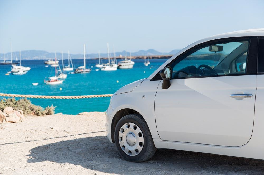 alquiler coche formentera. fiat blanco frente al mar azul y yates
