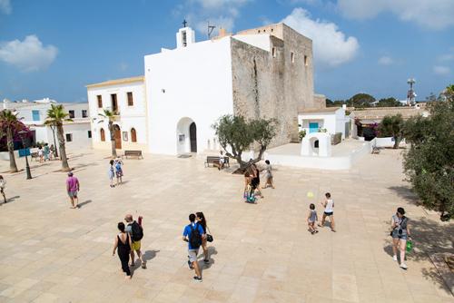 Turistas paseando delante de la iglesia del siglo XVIII en Sant Francesc, Formentera